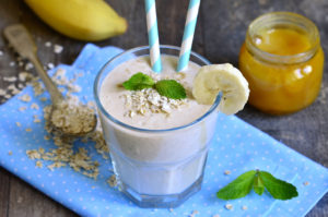 Banana smoothie with honey and oats on a wooden table.