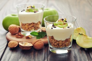 Homemade dessert with apple, nuts, yogurt and granola in glasses