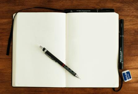 Åpen notisbok med penn.