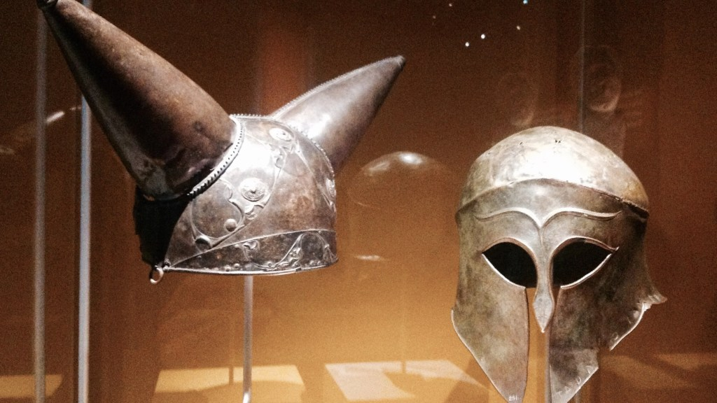 (L) Horned helmet. Bronze, glass, Found along the Thames river near Waterloo, London, England (200-100 BC). (R) Greek helmet, bronze. Olympia, South-Western Greece (460 BC), The British Museum.Photo by Medievalists.net.