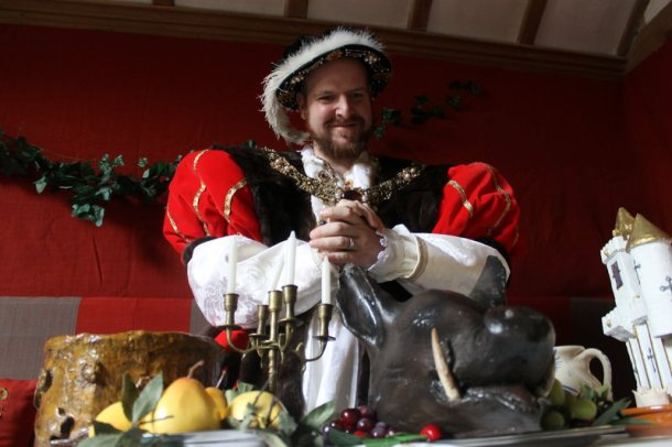 King Henry VIII (Nathan Wade) surveys the Tudor-feast inspired top table at Barley Hall, York. Photo courtesy  Jorvik Group