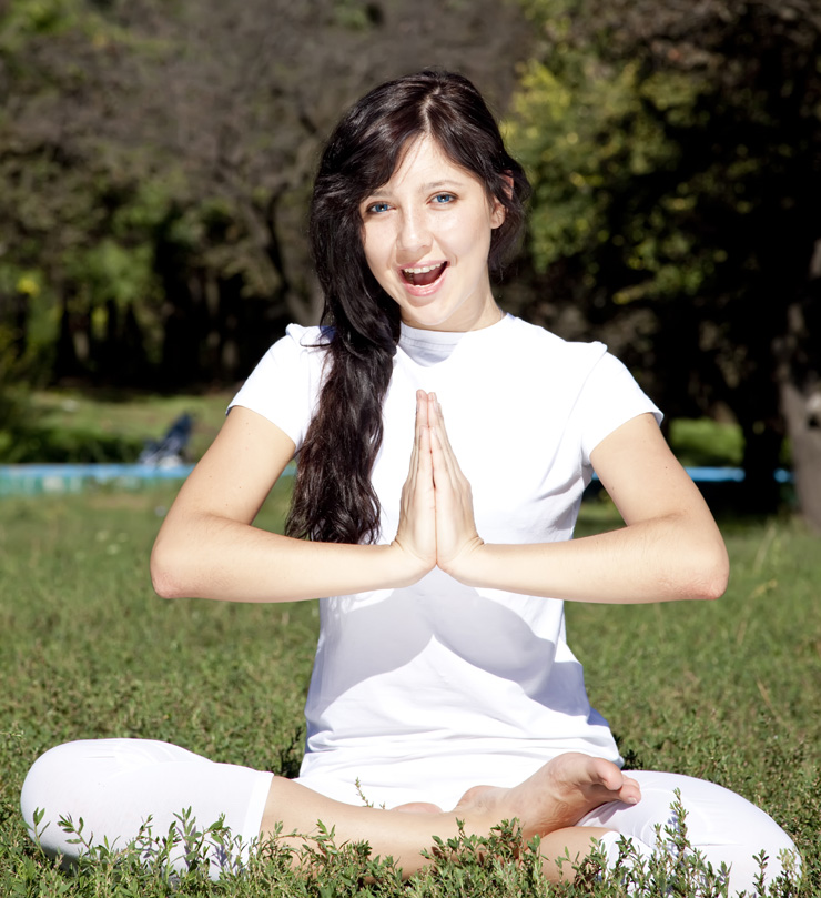 Beautiful young brunet yoga girl on green grass in park