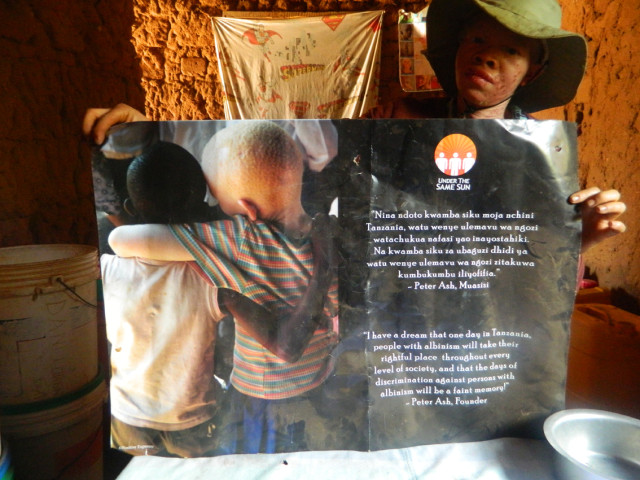 "Photo 2. A young woman in Ilula shows a poster produced by Under The Same Sun, which she has hung up in her house. She stated: ""We people with albinism are human beings (binadamu)."" 