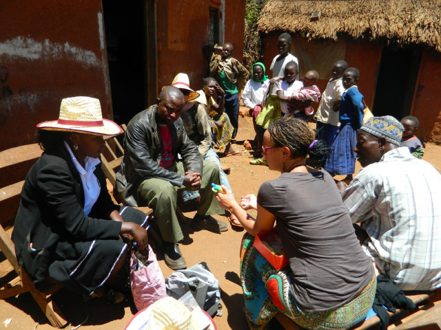 Photo 1. Distribution campaign of sunscreen and hats to people with albinism, carried out by volunteers of the NGO Tulime Onlus. In the photo, a volunteer is giving the major (mwenyekiti) of the village and a boy with albinism explanations on how to use the sunscreen. During the census I conducted on behalf of Tulime Onlus as a researcher-cum-employee, I distributed sunscreen, hats and sunglasses, while simultaneously collecting data on the life conditions of people with albinism in rural areas. | 2012 © Giorgio Brocco