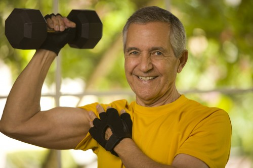 Senior man lifting a dumbbell an showing us his muscle