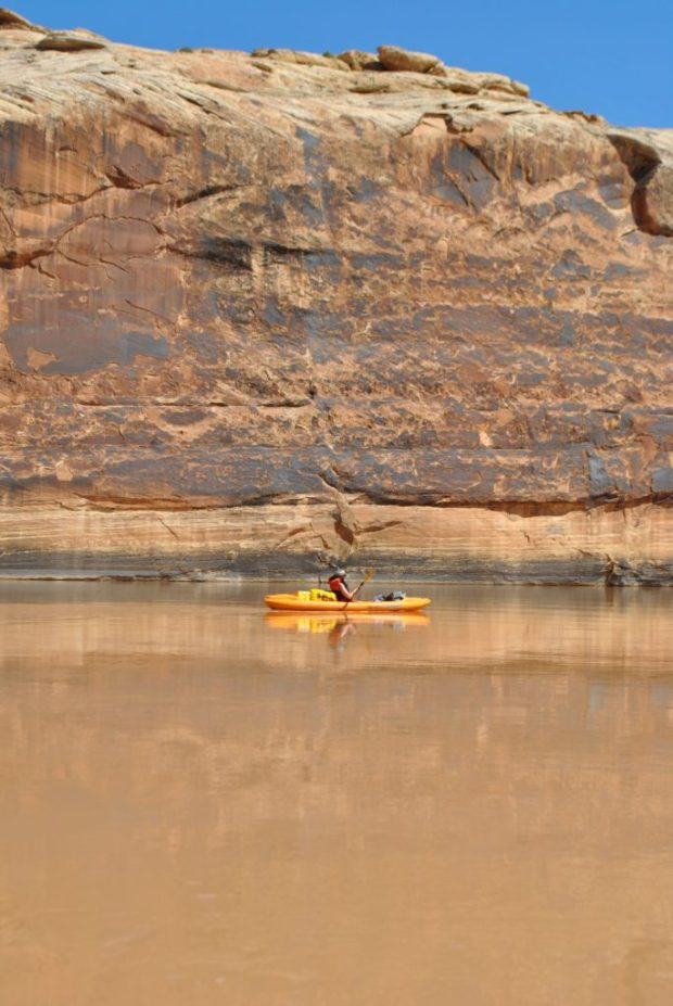 My Aunt Dianne paddling on still brown water beside a tall brown cliff on the Green River, Utah