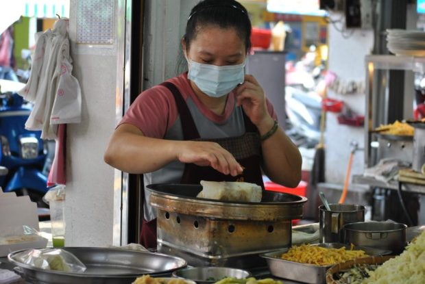 a woman with a hygienic face mask fries a Taiwanese spring roll at her stall