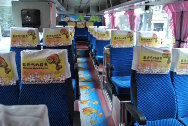 The empty interior of a Nanzhuang Tourist Bus in Taiwan with pink curtains and cartoon fish carpet
