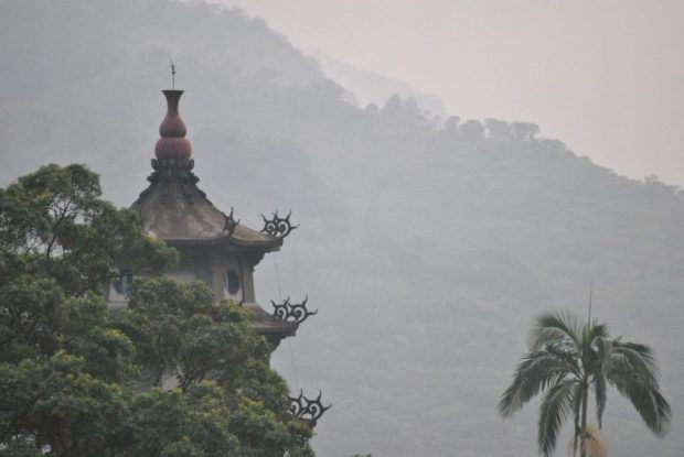 a grey pagoda rises out from the trees at Lion's Head Mountain, Taiwan
