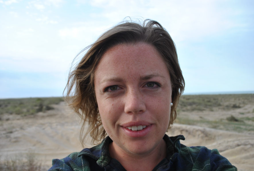 Me sitting in sand dunes near the Caspian Sea with my hair blowing