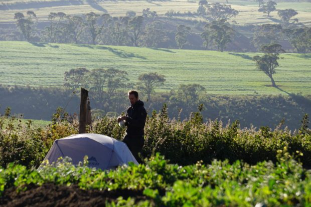 Evan and our tent in vivid green vegetable fields on the top of Mau Escarpment, Kenya
