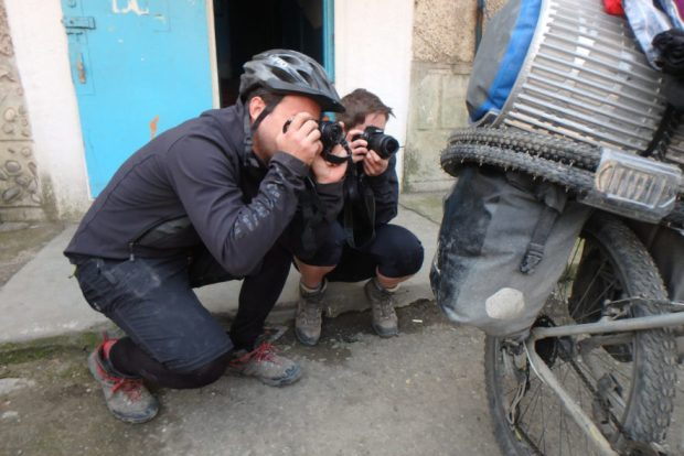 Evan and me crouch to take a photo of the same homemade winter bike tires in Osh, Kyrgyzstan