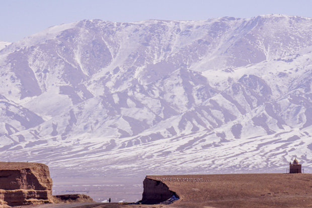 a wall of snowy mountains rising suddenly and me looking tiny on a bicycle as I pass through a roadcut in Kyrgyzstan