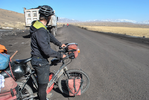 evan on the paved road looking towards a Kyrgyz boy and girl on bicycles