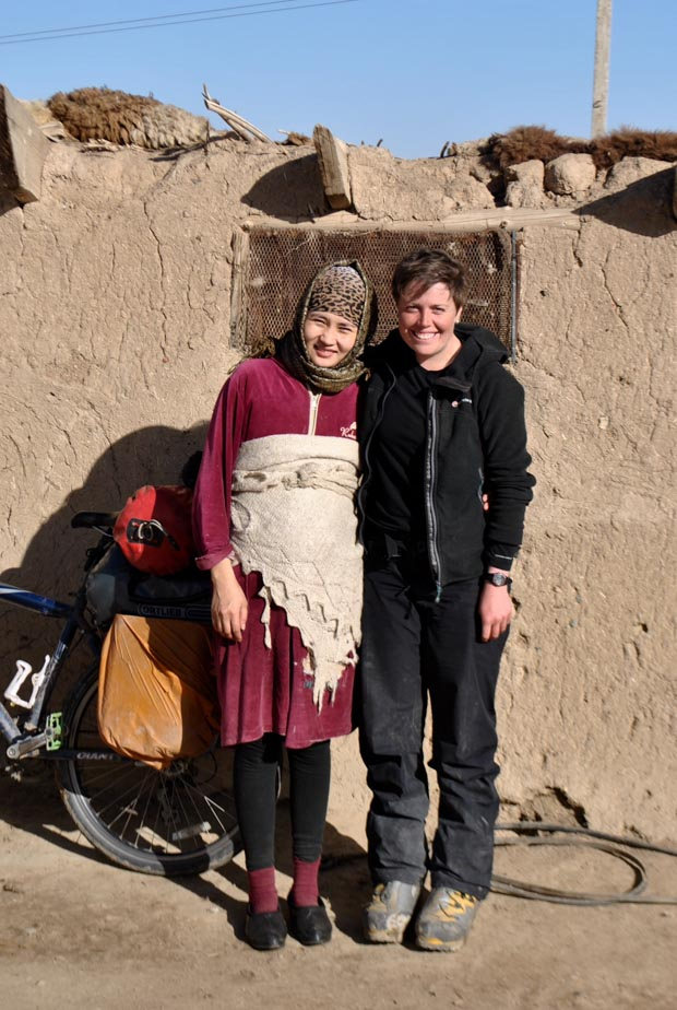 me and a Kyrgyz woman in a purple velvet dress and a shawl over her pregnant belly, standing outside her rural home in Naryn Province, Kyrgyzstan
