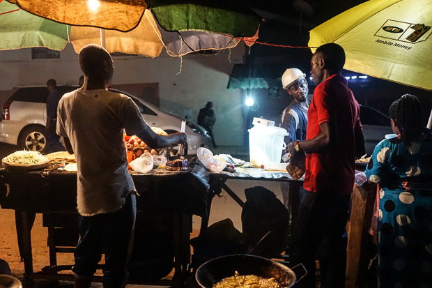 men operate their rolex stalls at night in fort portal uganda in front of waiting customers