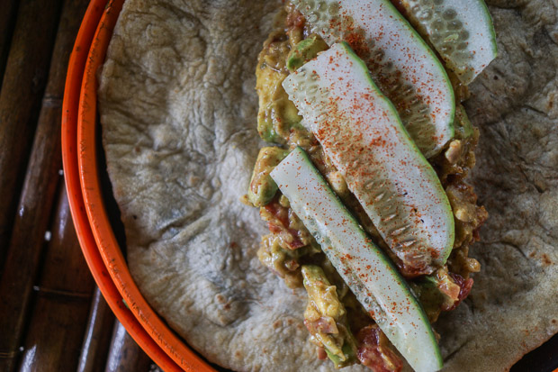 a close up picture of a chapati with guacamole and chopped cucumbers on it for our lunch at the crater lakes near fort portal uganda