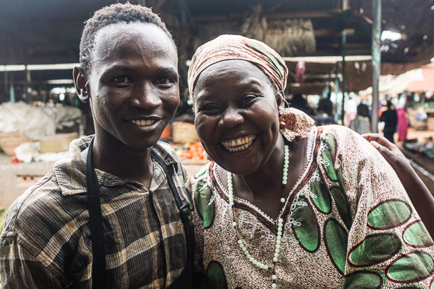a young ugandan man and his mother give a big smile at masindi public market