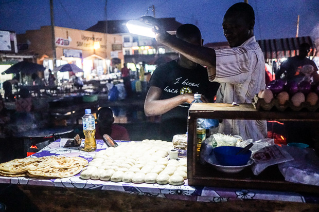 two men at their chapati stand in luweero uganda, shining a light down on their balls of chapati dough