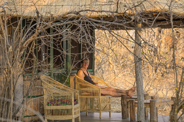 mom sitting on the porch of thatch cabin in Vwaza Marsh National Park, Kazuni Camp