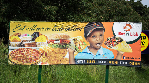 a young excited boy eating a taco on an Eat n' Lick billboard in Zimbabwe