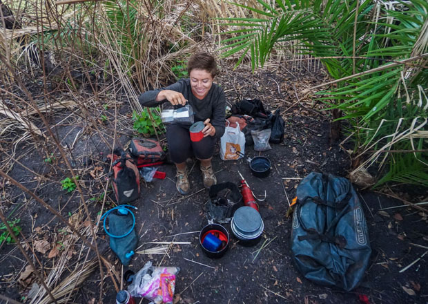 Me wild camping in palm trees in Uganda pouring coffee from a moka pot