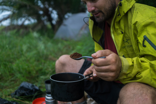 Evan wild camping in Mozambique, spooning coffee into a pot