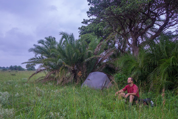 evan sits near a stand of palm trees where our tent is set up beside him, near the highway in southern Mozambique