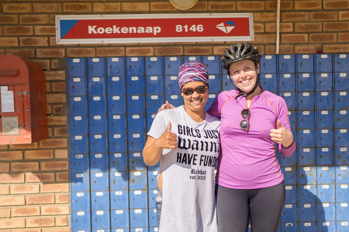 me and a woman outside blue post boxes in the dorpie of Kookenaap, South Africa