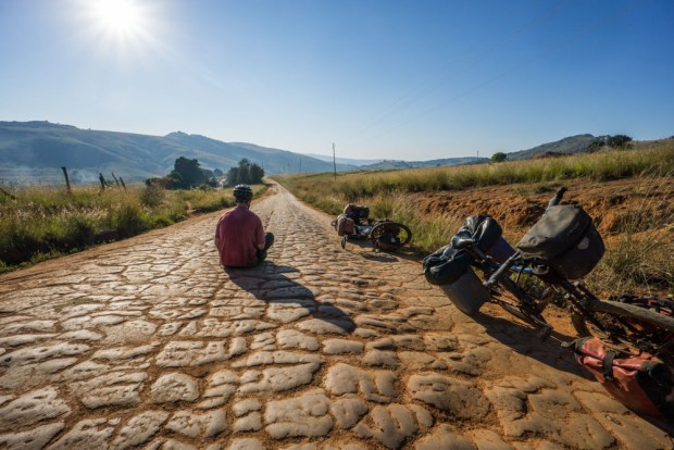 Evan sits on a cracked, patterned dirt road in Swaziland eSwatini
