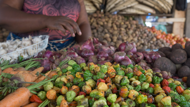 multicoloured hot peppers, red onions and beetroot piled high in a market in rural Tanzania