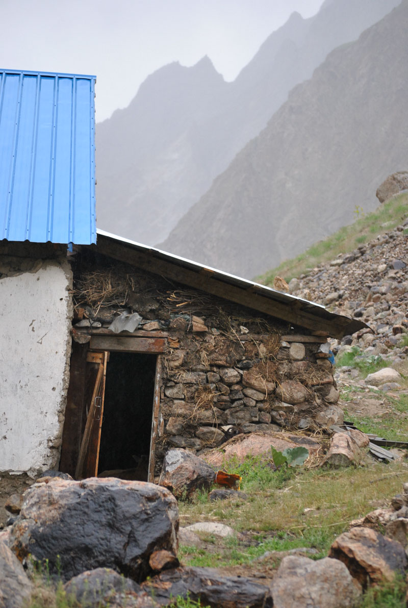 a rock slab home built into a steep hill on a misty day on the Pamir Highway, Tajikistan where we were hosted