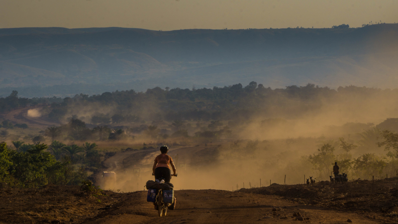 cycling down a dusty road in the late afternoon in Tanzania