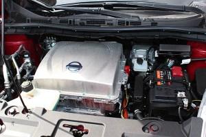 Hier sieht man rechts die Starterbatterie, der Stromspeicher für die Elektromotoren ist im Fahrzeugboden untergebracht. Hier sieht man den Motorraum eines Nissan Leaf.