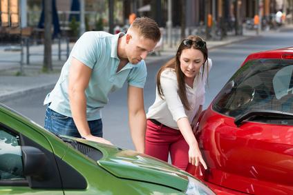 Eine junge Frau zeigt die Unfallschäden. Bildquelle: ©Andrey Popov. Fotolia.com