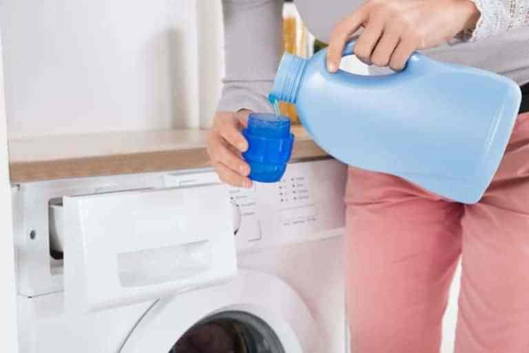 Jemand gießt Flüssigwaschmittel in eine Kappe