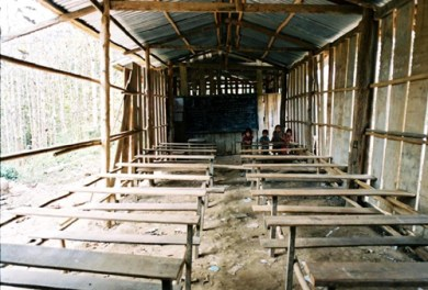 Classroom had a wall missing and a blackboard at each end with 2 teachers. Students had to move around the room to stay dry when it rained Who we are Who we are Ban Lad Khammune old school opt