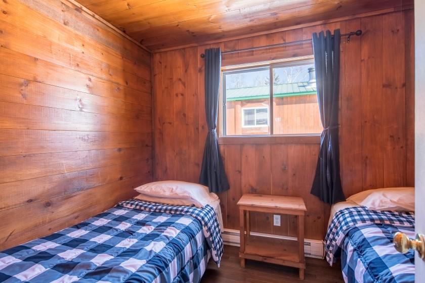 Chalet #8 de la Pourvoirie Mekoos. Chambre 1 avec un lit simple et un lit double
