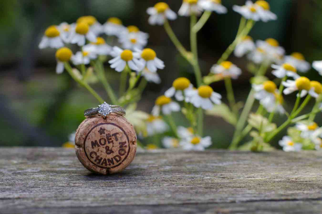Engagement ring balanced on top of a champagne cork with daisies in the background. Fife wedding