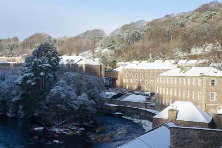 Photo of New Lanark Mill Hotel. Snow on the roof tops and the sun is shining. The river is running beside the buildings