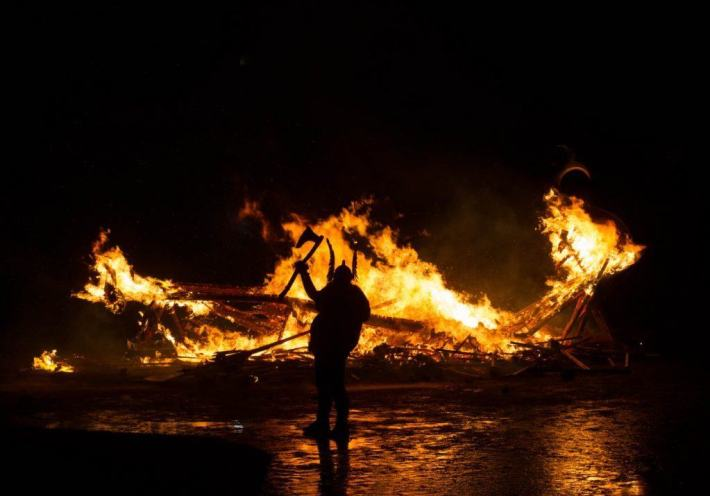 Up Helly Aa, Sheltand. Photo of the silhouette of the Guizer Jarl holding up an axe against the background of a burning Viking galley