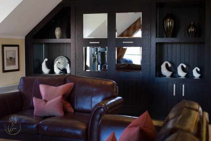 Photo of the living area. Dark wooden wall covering cabinet with four square mirrors on the doors. Shelves with ornaments