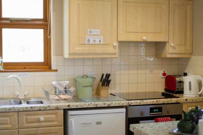 Photo of kitchen cupboards, cooker and worktops in self catering accommodation Morenish Mews