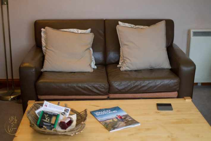 Photo of a two seater sofa and coffee table with books on at Morenish Mews