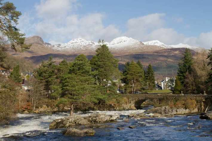 Photo of Falls of Dochart. River and a stone bridge in the foreground. Snowcapped mountains in the background and blue sky