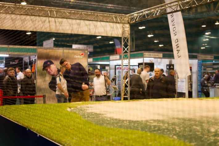 Photo of a man trying to get a golf ball out of a bunker at the Scottish Golf Show.