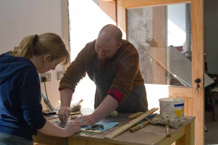 Photo of Keny Drew during a workshop helping out a student at a work bench
