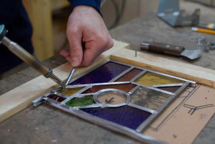 Photo of a person soldering a small stained glass window that is on the table.