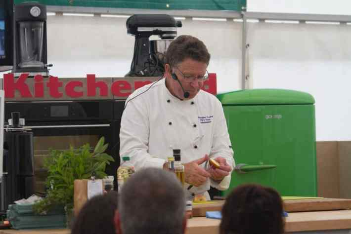 Photo of: Man in chef whites doing a cookery demonstration at the Scottish Game Fair