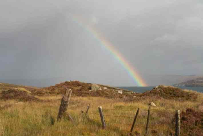 A rainbow over a loch in Scotland. In the foreground there is a broken wire fence and rocks